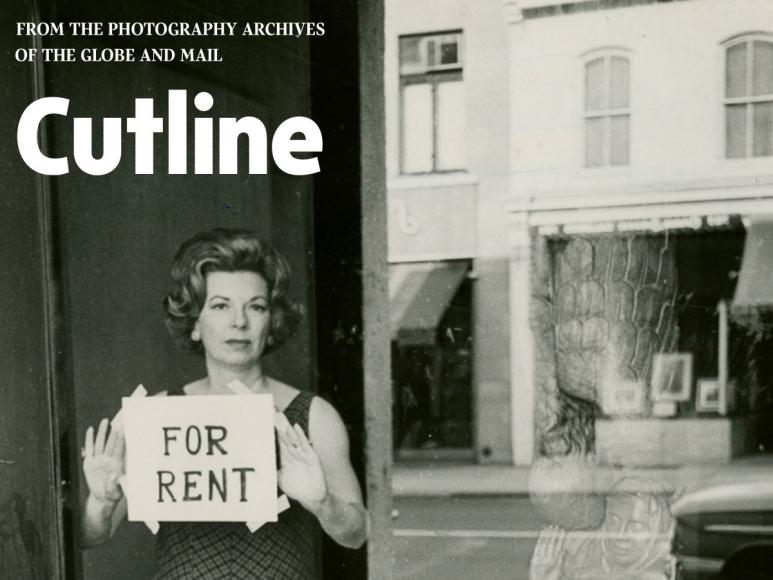 Black and white photo - Woman holding For Rent sign in window