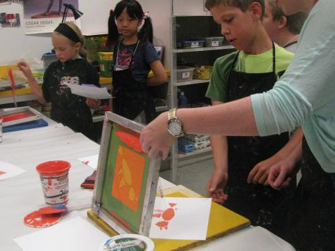 Children making prints with instructor