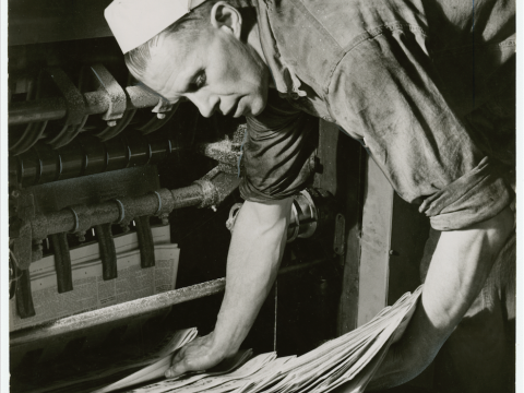 Black and white photo - Man picking up newspapers from printing machine