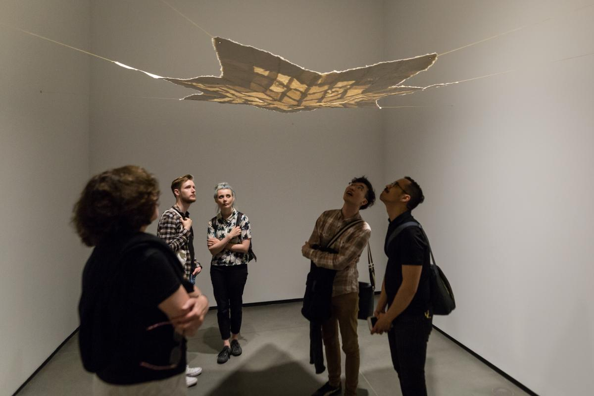 Gallery goers look up at a piece of art