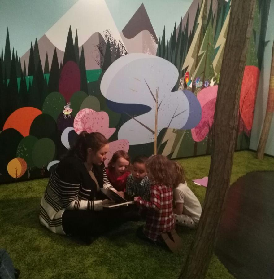 Circle of kids reading in the Wild Wood children's gallery