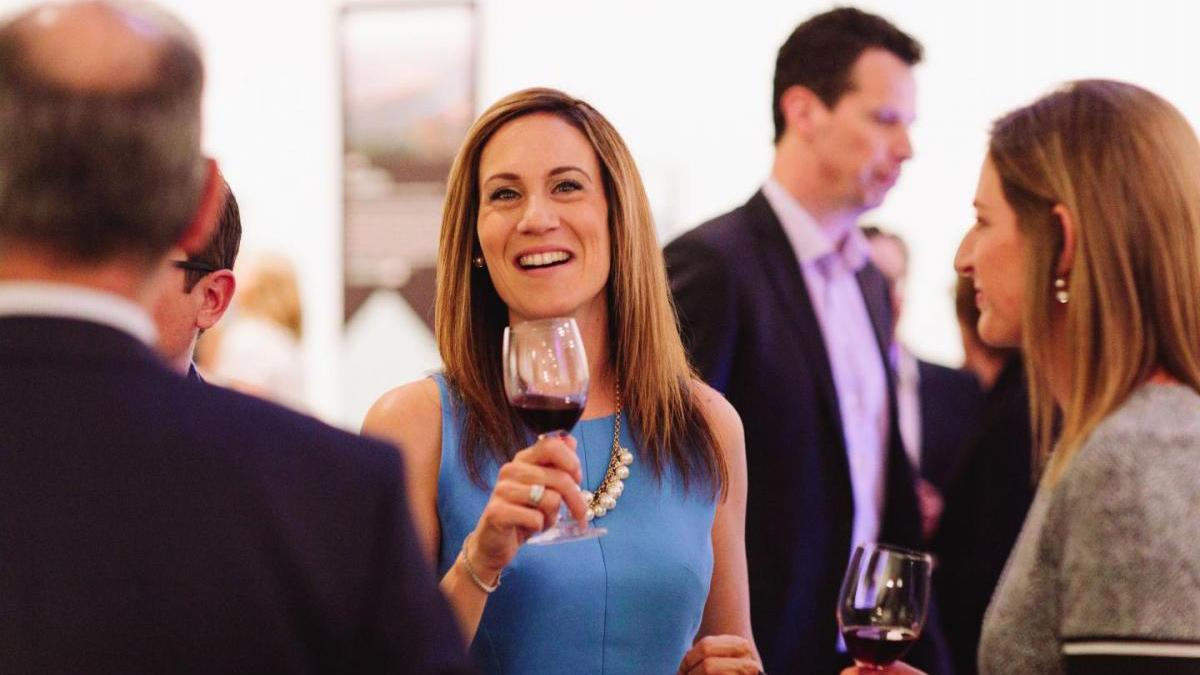 Woman holding a glass of wine at charity event