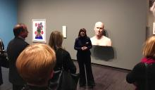 Curator speaking to group in front of statute